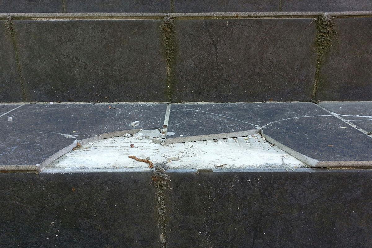Frostsprängda klinkerplattor som lossnat på yttertrappa