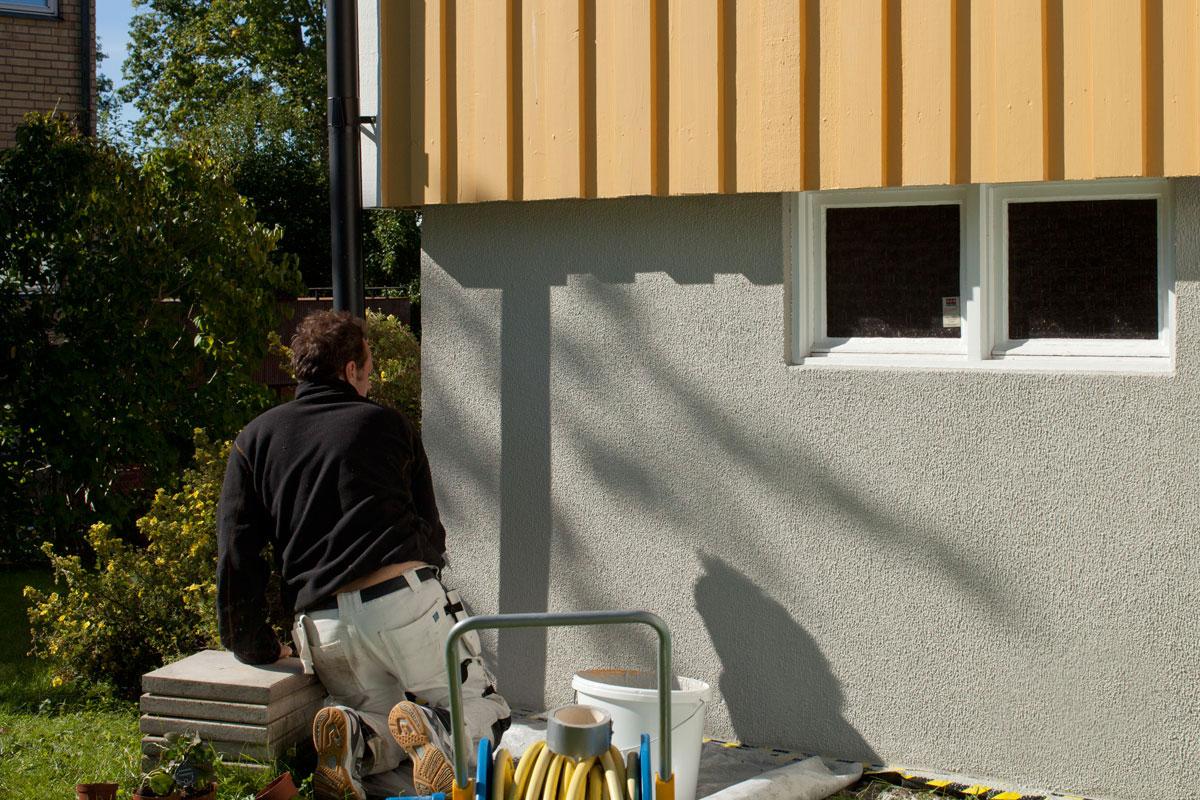 Målad husgrund som renoveras och putsas