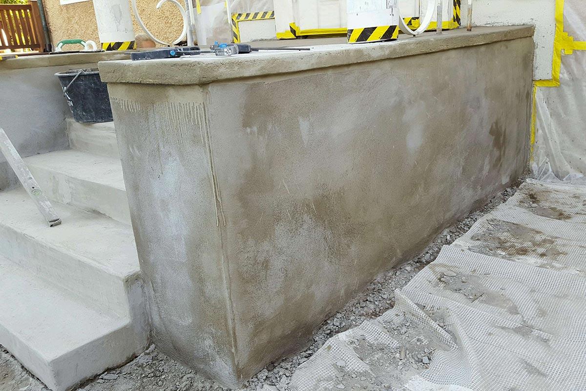 Putsad mur och gavelsidor under betongtrappa